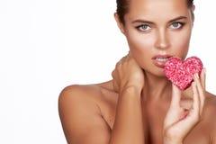 Όμορφη προκλητική γυναίκα brunette που τρώει τη μορφή κέικ του romanti καρδιών στοκ φωτογραφίες