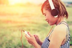Όμορφη προκλητική γυναίκα με την μπλε μουσική ακούσματος φορεμάτων μόνιμη μέσα Στοκ Εικόνες