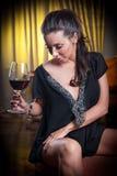Όμορφη προκλητική γυναίκα με το γυαλί της σκέψης κρασιού Στοκ Φωτογραφίες