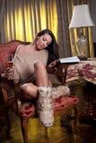 Όμορφη προκλητική γυναίκα με το ποτήρι του κρασιού που διαβάζει μια συνεδρίαση βιβλίων στην καρέκλα Στοκ Εικόνες