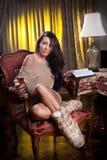 Όμορφη προκλητική γυναίκα με το ποτήρι του κρασιού που διαβάζει μια συνεδρίαση βιβλίων στην καρέκλα Στοκ Φωτογραφία
