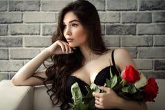 Όμορφη προκλητική γυναίκα brunette πορτρέτου με τα τριαντάφυλλα στα χέρια Στοκ εικόνες με δικαίωμα ελεύθερης χρήσης