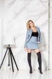 Όμορφη προκλητική επιχειρησιακή ξανθή τοποθέτηση σε ένα μαρμάρινο υπόβαθρο Στοκ φωτογραφία με δικαίωμα ελεύθερης χρήσης
