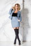 Όμορφη προκλητική επιχειρησιακή ξανθή τοποθέτηση σε ένα μαρμάρινο υπόβαθρο Στοκ Φωτογραφία