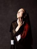 Όμορφη προκλητική καθολική τοποθέτηση καλογριών σε ένα σκοτεινό υπόβαθρο Θρησκευτική έννοια Στοκ Εικόνες