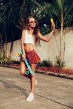 Όμορφη προκλητική νέα κυρία στην ερωτική μίνι φούστα με skateboard Στοκ εικόνες με δικαίωμα ελεύθερης χρήσης