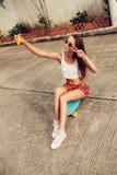 Όμορφη προκλητική νέα κυρία στην ερωτική μίνι φούστα με skateboard Στοκ Εικόνα