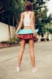 Όμορφη προκλητική νέα κυρία στην ερωτική μίνι φούστα με skateboard Στοκ Φωτογραφίες