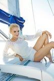 Όμορφη προκλητική νέα ξανθή γυναίκα, που οδηγά μια βάρκα στο νερό, περιήγηση, όμορφο makeup, ιματισμός, καλοκαίρι, ήλιος, τέλειο  Στοκ Εικόνα