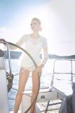 Όμορφη προκλητική νέα ξανθή γυναίκα, που οδηγά μια βάρκα στο νερό, περιήγηση, όμορφο makeup, ιματισμός, καλοκαίρι, ήλιος, τέλειο  Στοκ Εικόνες