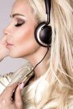 Όμορφη προκλητική ξανθή γυναίκα με το μακρυμάλλες και τέλειο σώμα στο μαύρο σακάκι δέρματος με τα ακουστικά Στοκ φωτογραφία με δικαίωμα ελεύθερης χρήσης