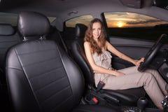 Όμορφη προκλητική συνεδρίαση κοριτσιών πίσω από τη ρόδα ενός αυτοκινήτου υπαίθρια Στοκ Φωτογραφίες