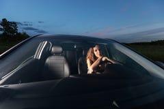 Όμορφη προκλητική συνεδρίαση κοριτσιών πίσω από τη ρόδα ενός αυτοκινήτου που εξετάζει τη κάμερα υπαίθρια Στοκ φωτογραφίες με δικαίωμα ελεύθερης χρήσης