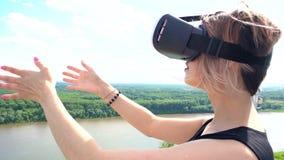 Όμορφη προσομοίωση γυναικών στο υπαίθριο πάρκο με τη συσκευή κασκών εικονικής πραγματικότητας VR απόθεμα βίντεο
