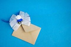 Όμορφη πρόσκληση για το γεγονός γάμου ή γενεθλίων Καφετής φάκελος με το διακοσμητικό τόξο Στοκ Εικόνες