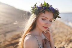 Όμορφη πρότυπη γυναίκα με τέλειο Makeup, τη μακριά σγουρά τρίχα και το στεφάνι των λουλουδιών Στοκ Φωτογραφία