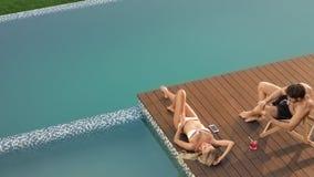 Όμορφη πρότυπη ηλιοθεραπεία στο poolside με το φίλο Ισχυρό άτομο που παίρνει την εικόνα απόθεμα βίντεο