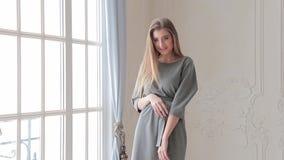 Όμορφη πρότυπη τοποθέτηση μόδας στο γκρίζο φόρεμα κοντά στο παράθυρο απόθεμα βίντεο