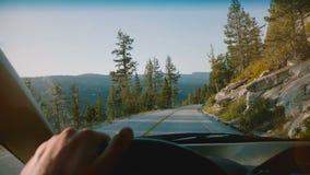 Όμορφη πρώτη άποψη προσώπων της αρσενικής οδήγησης τιμονιών αυτοκινήτων εκμετάλλευσης χεριών κατά μήκος του δρόμου βουνών σε Yose φιλμ μικρού μήκους