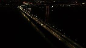 Όμορφη πόλη νύχτας και μια ογκώδης γέφυρα, μέρη των αυτοκινήτων, φω'τα πυράκτωσης, εναέριος πυροβολισμός φιλμ μικρού μήκους