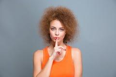 Όμορφη σγουρή γυναίκα που παρουσιάζει σημάδι σιωπής Στοκ εικόνες με δικαίωμα ελεύθερης χρήσης