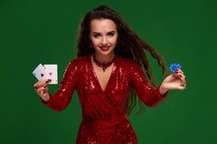 Όμορφη σγουρή γυναίκα σε ένα ακτινοβολημένο φόρεμα, που κρατά μερικές κάρτες παιχνιδιού και παιχνίδι των τσιπ casino στοκ φωτογραφία