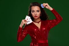 Όμορφη σγουρή γυναίκα σε ένα ακτινοβολημένο φόρεμα, που κρατά μερικές κάρτες παιχνιδιού και παιχνίδι των τσιπ casino στοκ εικόνα