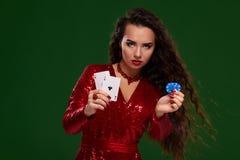 Όμορφη σγουρή γυναίκα σε ένα ακτινοβολημένο φόρεμα, που κρατά μερικές κάρτες παιχνιδιού και παιχνίδι των τσιπ casino στοκ εικόνα με δικαίωμα ελεύθερης χρήσης