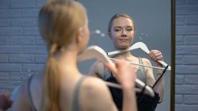Όμορφη σκέψη γυναικών την επιλογή φορεμάτων που φαίνεται καθρέφτης μπουτίκ, προετοιμασία γεγονότος απόθεμα βίντεο