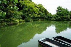 Όμορφη σκηνή του πολύβλαστου πράσινου ιαπωνικού βουνού κήπων με τις σκιές των πράσινων εγκαταστάσεων, των βαρκών, της λίμνης λωτο Στοκ Εικόνες