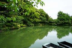 Όμορφη σκηνή του πολύβλαστου πράσινου ιαπωνικού τοπίου βουνών κήπων με τις σκιές των πράσινων εγκαταστάσεων, των βαρκών, της λίμν Στοκ εικόνες με δικαίωμα ελεύθερης χρήσης