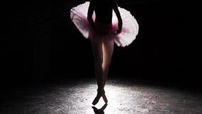 Όμορφη σκιαγραφία του νέου ballerina στα παπούτσια pointe στο μαύρο συγκεκριμένο υπόβαθρο πατωμάτων Πρακτική μπαλέτου Η γυναίκα π απόθεμα βίντεο