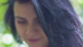 Όμορφη σκοτεινή τρίχα της καλής γυναίκας, πρόσωπο χαμόγελου του θηλυκού υπαίθρια, ντροπαλή κυρία απόθεμα βίντεο