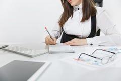 Όμορφη σοβαρή συνεδρίαση επιχειρησιακών γυναικών στο γραφείο, που λειτουργεί στον υπολογιστή με τα έγγραφα στο ελαφρύ γραφείο Στοκ Εικόνες