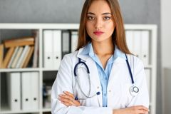 Όμορφη στάση γιατρών χαμόγελου θηλυκή στο πορτρέτο γραφείων Στοκ εικόνα με δικαίωμα ελεύθερης χρήσης