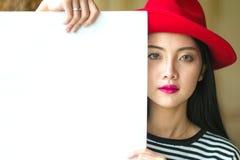 Όμορφη στάση γυναικών, που κρατά το λευκό κενό διαφημιστικό πίνακα Στοκ Εικόνες