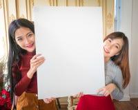 Όμορφη στάση γυναικών, που κρατά το λευκό κενό διαφημιστικό πίνακα Στοκ Φωτογραφίες