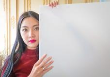 Όμορφη στάση γυναικών, που κρατά το λευκό κενό διαφημιστικό πίνακα Στοκ φωτογραφία με δικαίωμα ελεύθερης χρήσης