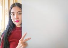 Όμορφη στάση γυναικών, που κρατά το λευκό κενό διαφημιστικό πίνακα Στοκ φωτογραφίες με δικαίωμα ελεύθερης χρήσης