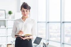 Όμορφη στάση επιχειρηματιών στην αρχή, κρατώντας το σημειωματάριο, προγραμματίζοντας συνεδριάσεις για την ημέρα εργασίας, που εξε στοκ εικόνα με δικαίωμα ελεύθερης χρήσης