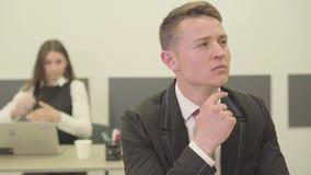 Όμορφη στοχαστική συνεδρίαση νεαρών άνδρων πορτρέτου στο πρώτο πλάνο στο γραφείο ενώ η γυναίκα συνάδελφός του στην επίσημη ένδυση φιλμ μικρού μήκους