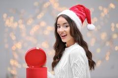 Όμορφη συγκινημένη κυρία στο κιβώτιο δώρων ανοίγματος καπέλων Χριστουγέννων Στοκ Εικόνα