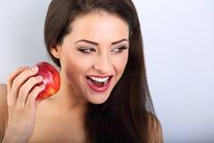 Όμορφη συγκινημένη makeup γυναίκα brunette που κρατά το κόκκινο νόστιμο μήλο Στοκ εικόνες με δικαίωμα ελεύθερης χρήσης
