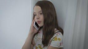 Όμορφη συναισθηματική ομιλία μικρών κοριτσιών στο έξυπνο τηλέφωνο από το παράθυρο απόθεμα βίντεο