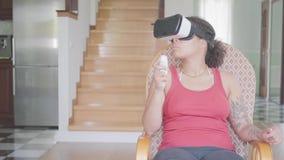 Όμορφη συνεδρίαση γυναικών αφροαμερικάνων στην πολυθρόνα στο σπίτι στην κάσκα εικονικής πραγματικότητας, που κοιτάζει μακριά Το κ φιλμ μικρού μήκους