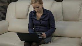 Όμορφη συνεδρίαση γυναικών σε έναν καναπέ στο σπίτι και σε απευθείας σύνδεση χρησιμοποιώντας πιστωτική κάρτα φορητών προσωπικών υ απόθεμα βίντεο