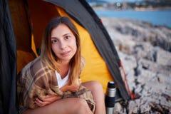 Όμορφη συνεδρίαση γυναικών στην άσπρη παραλία πετρών, ενδιαφερόμενη εξέταση την πλευρά στοκ εικόνα με δικαίωμα ελεύθερης χρήσης