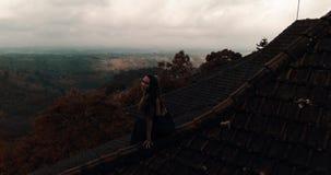 Όμορφη συνεδρίαση γυναικών στην κόκκινη στέγη σπιτιών απόθεμα βίντεο