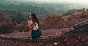 Όμορφη συνεδρίαση γυναικών στην κόκκινη στέγη σπιτιών φιλμ μικρού μήκους