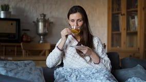 Όμορφη συνεδρίαση γυναικών στον καναπέ που τυλίγεται σε ένα κάλυμμα και ένα τσάι κατανάλωσης φιλμ μικρού μήκους